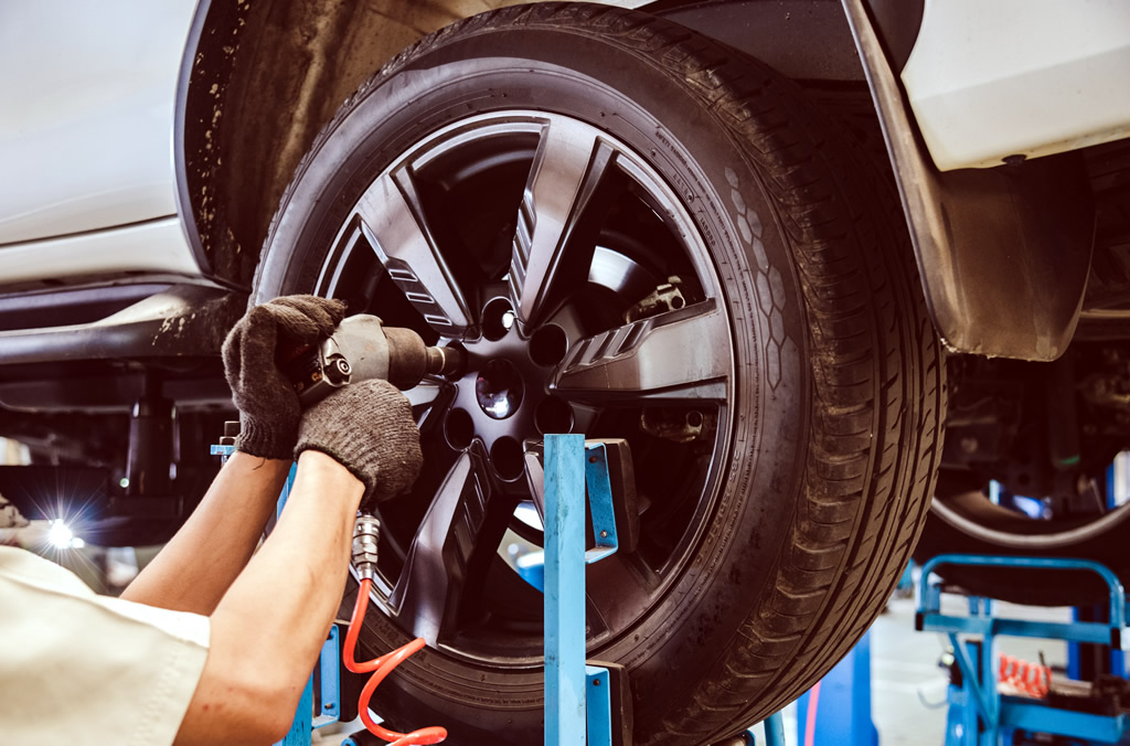 One of our technicians changes the wheel of a customer's car.